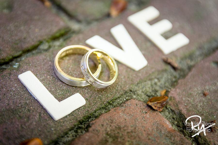 Fotografie trouwringen speels love gouden ringen